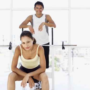 young man standing behind a young woman in a gym