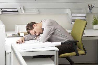 Young businessman asleep on desk