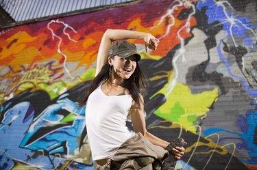 Woman street dancing by graffiti mural