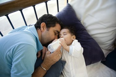 High angle view of a mature man feeding his baby with a bottle
