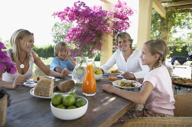 Parents and children (9-11) eating at table on villa terrace, smiling