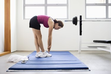 Young woman doing stretching exercise on mat in gym