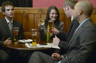 Businesswoman having drinks with three male colleagues in bar, smiling