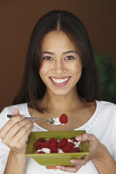 Asian woman eating fruit and cream