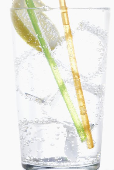 Straws, lemon and ice in carbonated water