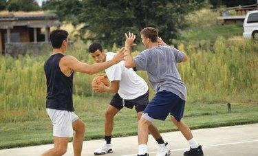 Three teenage boys (16-17) playing basketball on outdoor court
