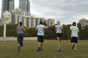 Young men and women jogging in park, rear view
