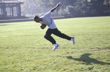 Teenage boy running with football in park