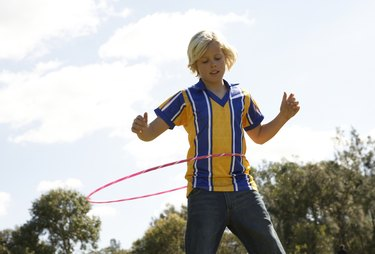 Boy (12-13) playing with plastic hoop in park