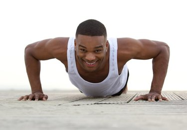 Close up portrait of a smiling man doing push ups