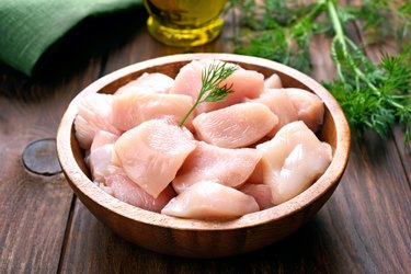 Chicken meat in wooden bowl