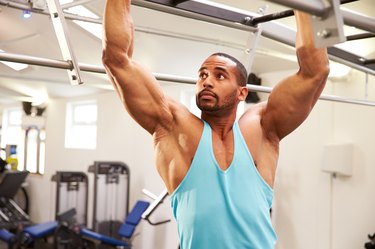 Muscular man flexing muscles on monkey bars at a gym