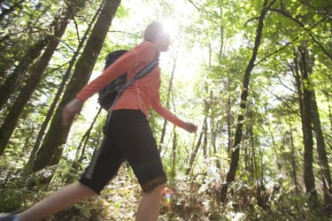 Woman hiking up hill in forest in sunlight
