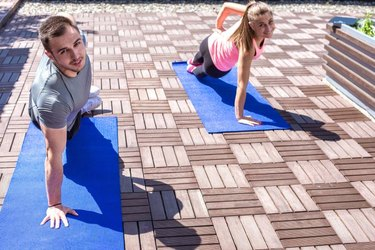 Young couple doing together side plank exercise on the rooftop, outdoors.