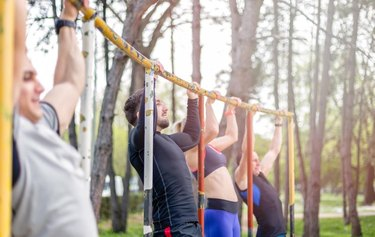 group of young people are competing doing pull ups in local park