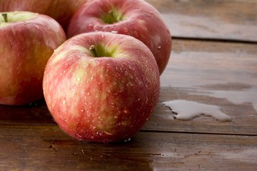 Honeycrisp apples on a wood background.