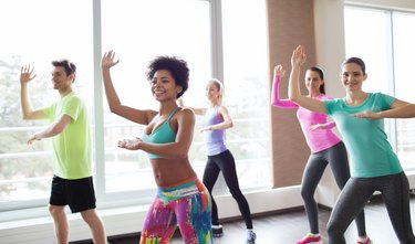 A group of smiling people in an aerobics class
