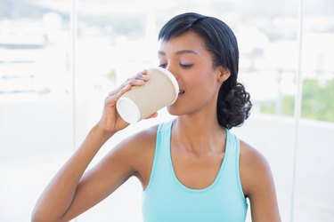 Pleased black haired woman drinking coffee