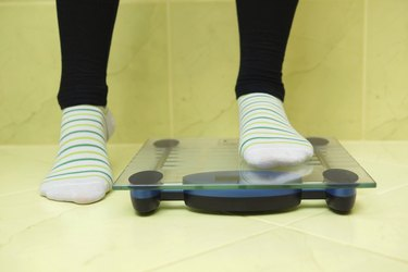woman wants to weigh and stands on the scales