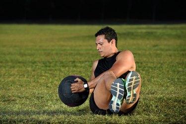 sport man workout on green grass lifting big ball