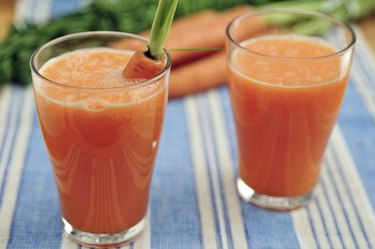 Ginger carrot juice in glass on blue and white table