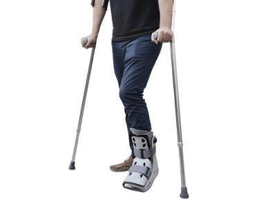 broken leg man wearing ankle support with walking crutches