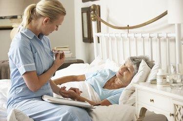 Nurse Taking Pulse Of Senior Patient  In Bed