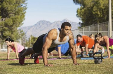 Strong man leading push-ups with exercise group