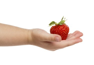 Child's hand with strawberries.