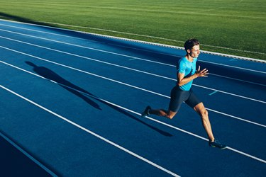 Young male athlete training on a race track