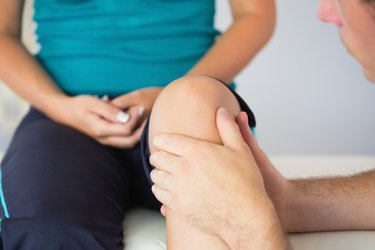 Physiotherapist checking patients knee