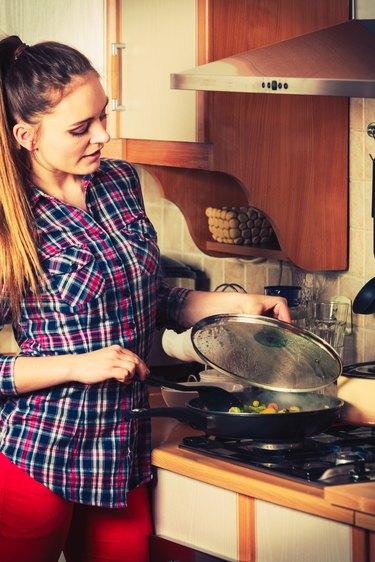 Woman frying frozen vegetables. Stir fry.