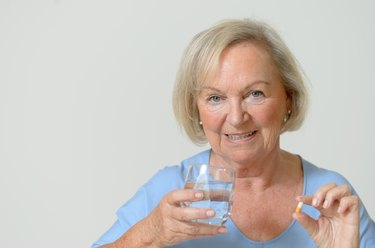 Elderly lady taking the prescribed dose of medicine