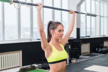 young sporty woman doing weightlifting exercises, fit female working out with barbell.