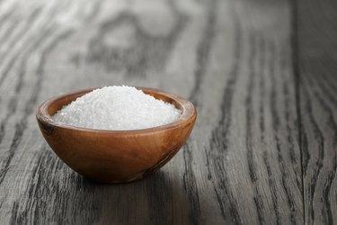 White sugar in olive wood bowl