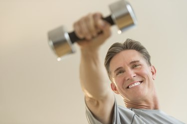 Happy Man Lifting Dumbbell Against Beige Background