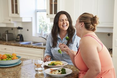 Two Overweight Women On Diet Eating Healthy Meal In Kitchen