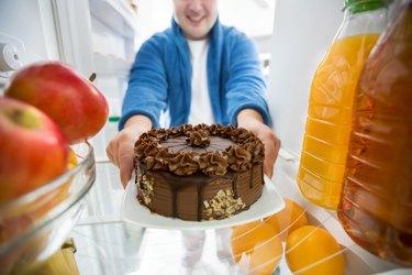 Boy take chocolate cake from fridge
