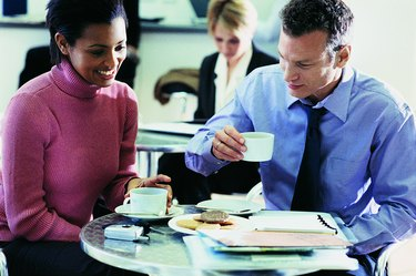 Two Business Colleagues Sitting in a Canteen Having a Cup of Coffee