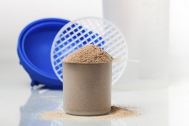 Chocolate whey isolate protein scoop in front of shaker