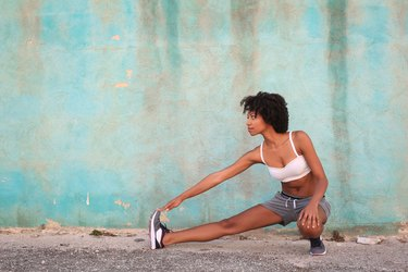 Sportive girl stretching her leg