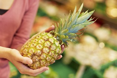 Germany, Cologne, Young woman with pineapple in supermarket