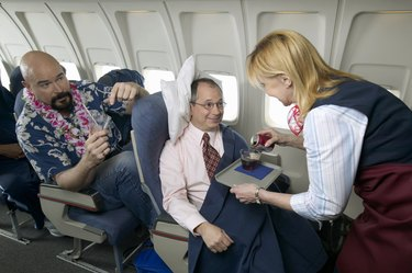 Air Stewardess Pouring a Drink For a Businessman on a Plane