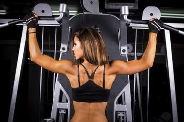Female Athlete Doing Pull Ups (Chin-Ups) in the Gym