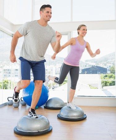 Couple doing step aerobics in fitness studio