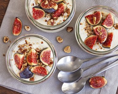 Three bowls of yogurt with figs and walnuts on a linen napkin