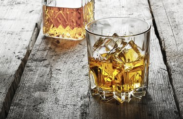 Faceted glass of whiskey with ice and a decanter