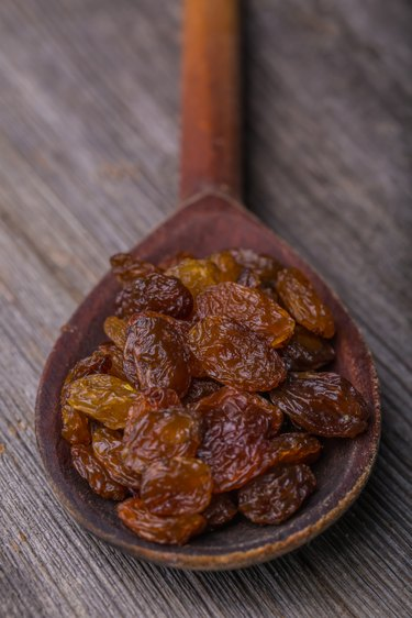 Raisins in a old wooden spoon