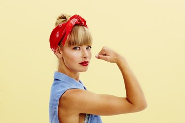 Strong young blond woman flexing muscle, portrait