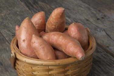 Sweet Potatoes in Basket on Wood Table
